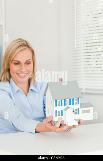 Smiling businesswoman showing model house - Stock Image