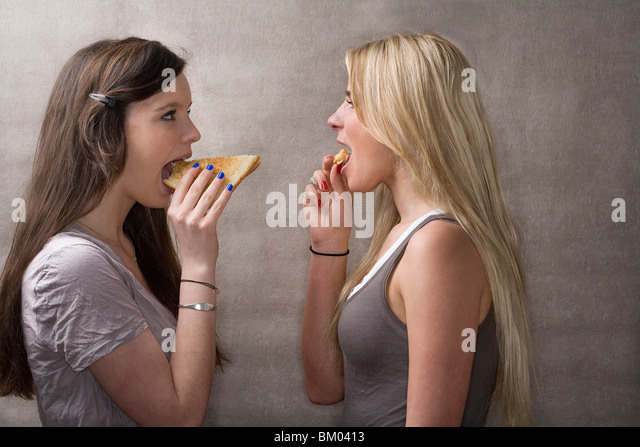 Teen girls eat sandwiches - Stock-Bilder