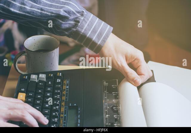 Man writing in a vintage typewriter - Stock Image