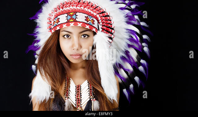 Studio portrait of woman wearing Native American headdress - Stock-Bilder
