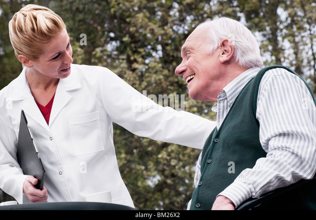 Man smiling with a doctor - Stock Image