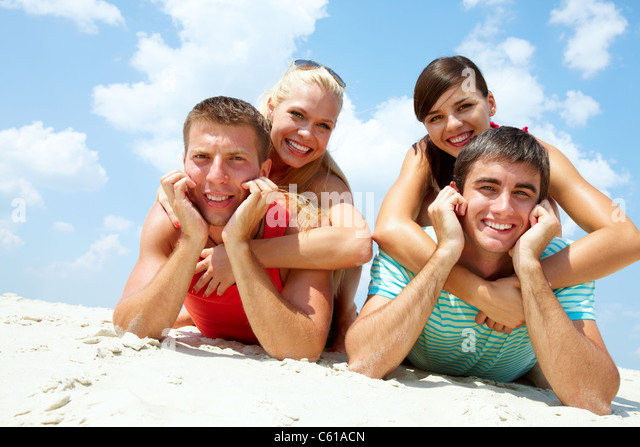 Two happy couples lying on sand and looking at camera - Stock Image