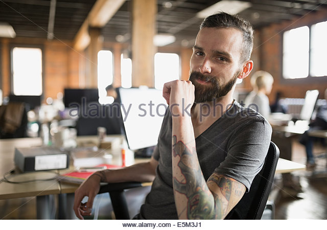 Portrait of confident businessman with tattoos in office - Stock-Bilder
