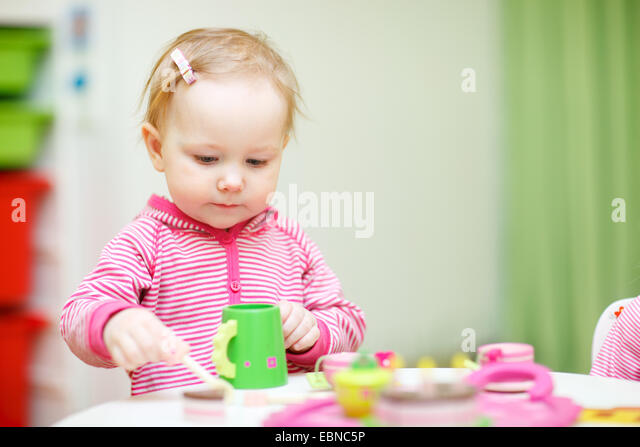 little girl plays drink coffee with plastic toys - Stock-Bilder