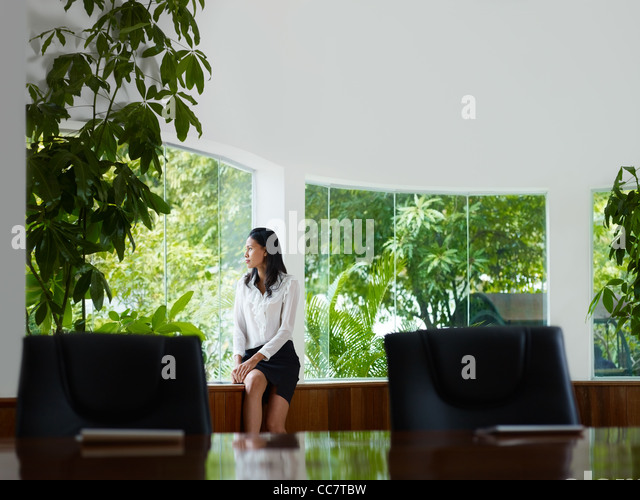 Beautiful Asian female manager looking out of the window in office. Front view, copy space - Stock Image