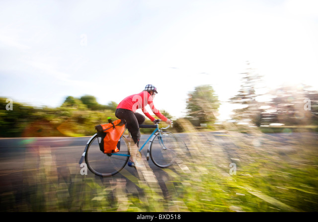 A blurry image of a young woman riding her a bike around a park at sunset. - Stock Image