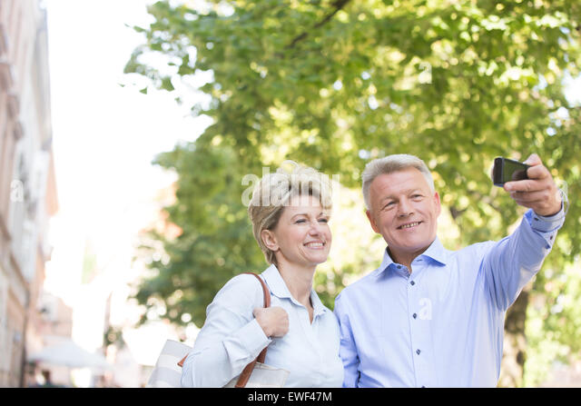 Happy middle-aged couple taking selfie outdoors - Stock Image