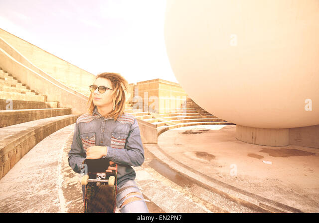 portrait of young guy  with skate and rasta hair in a lifestyle concept - Stock-Bilder