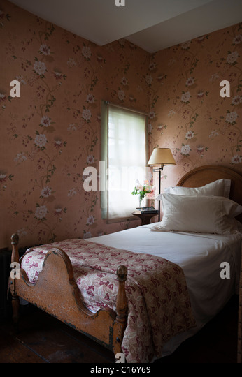 Single bed in 1830s Hudson Valley farmhouse bedroom with patterned wallpaper - Stock Image