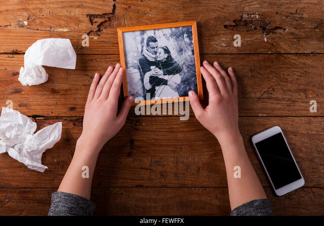 Unrecognizable sad woman holding broken picture of couple in love. - Stock-Bilder