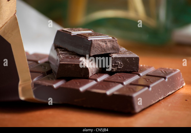 Dark chocolate bar in wrapper. - Stock Image