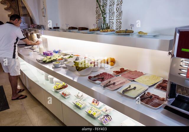 Spain Europe Spanish Hispanic Toledo Carlos V hotel inside interior breakfast buffet Hispanic man self-service serving - Stock Image