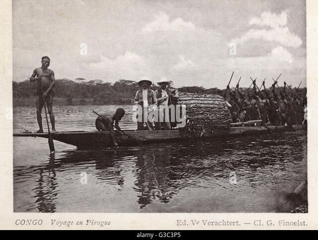 White men and natives travelling in a pirogue (a type of boat) in the Belgian Congo, Central Africa.      Date: - Stock-Bilder