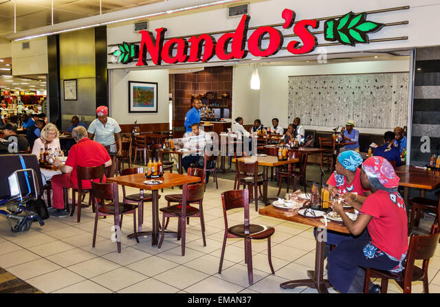 Johannesburg South Africa African O. R. Tambo International Airport terminal concourse gate area restaurant Nando's - Stock Image
