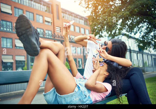Woman stretched on bench with friend take photo outside by tall fence under a wide tree - Stock Image