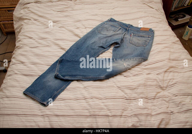 Worn blue jeans on a bed quilt - Stock Image