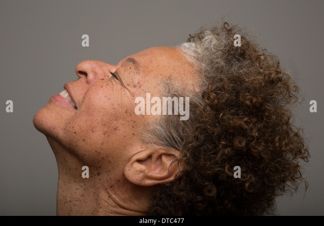 Close up studio portrait of senior woman with head back and eyes closed - Stock Image