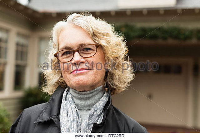 Portrait of happy senior woman outside house - Stock Image