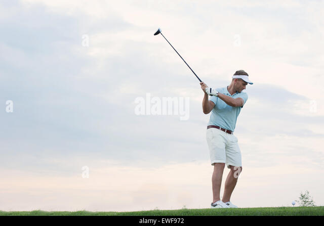 Mid-adult man playing golf against sky - Stock Image