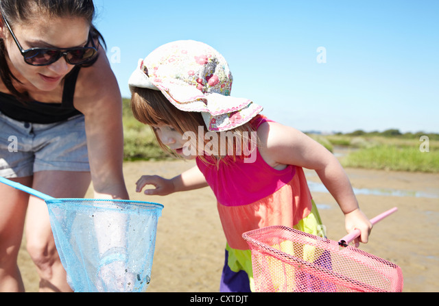 Mother and daughter fishing with nets - Stock Image