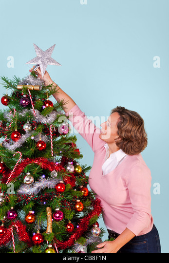 Photo of a woman at home decorating her Christmas tree and finishing off by putting the star on top. - Stock Image