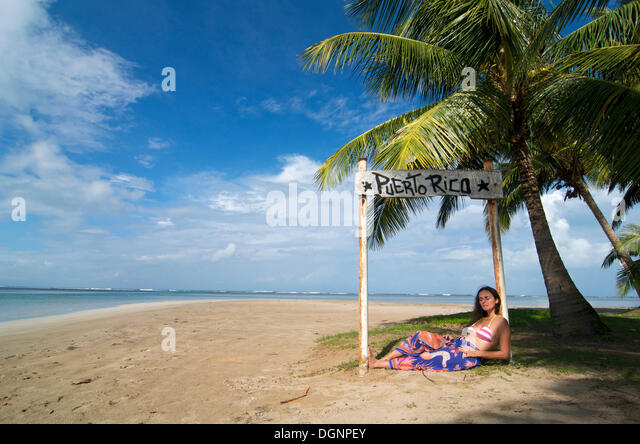 Tourist lying under a sign with the words Puerto Rico, Luquillo Beach, Puerto Rico, Caribbean - Stock Image