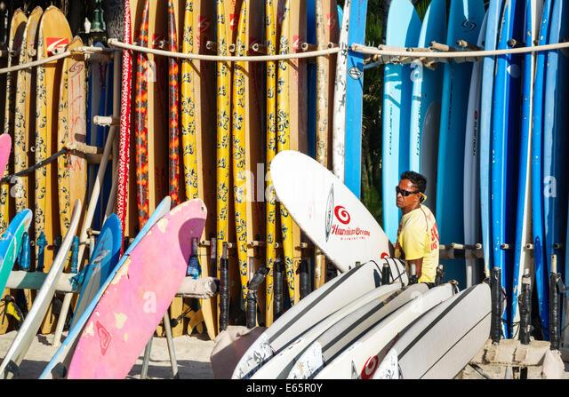Hawaii Hawaiian Honolulu Waikiki Beach resort Kuhio Beach State Park Pacific Ocean rental surfboards rent man - Stock Image