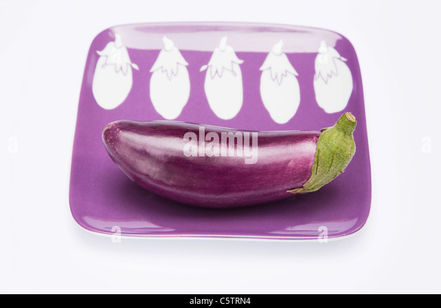 Raw Eggplant (Solanum melongena) on plate - Stock Image