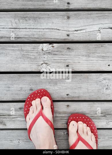 Red flip flops on a wooden wharf - Stock Image