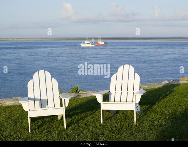 two white Adirondack chairs on lawn by the bay - Stock-Bilder
