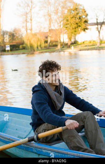 Man rowing row boat - Stock Image