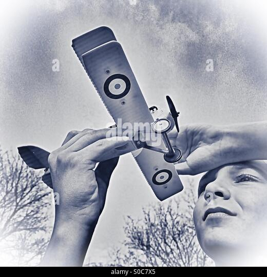 Black and white sketch style of boy gazing at his model plane against the backdrop of sky - Stock Image
