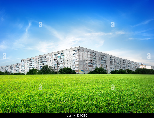 Field of green grass in front of the city - Stock Image