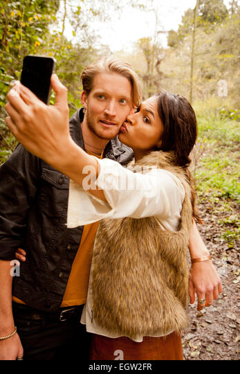Woman and man taking a selfie in the woods. - Stock Image