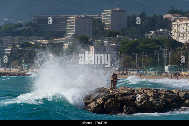 Waves crash against rocks on a beach in Cannes, South of France. - Stock Image