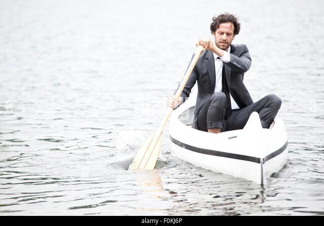 Germany, Rur Reservoir, businessman paddling in canoe - Stock Image