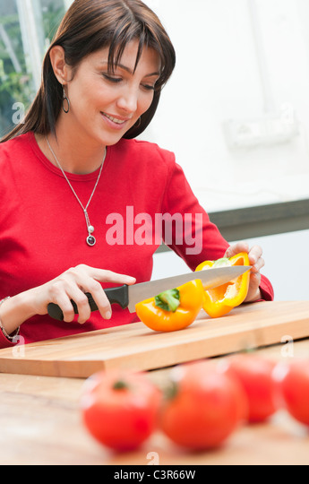 Cutting yellow pepper at kitchen - Stock Image