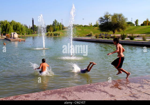 Argentina Mendoza Parque General San Martin public park artificial lake water Hispanic boy teen swimming swim cool - Stock Image