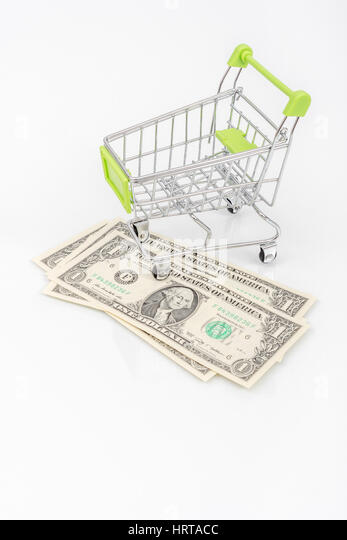 Shopping cart over several US $1 / one dollar banknotes on a light background. Mepahor for US retail sales, spending - Stock Image