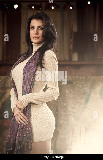 Fashion styled portrait of woman in dress with scarf standing in abandoned building - Stock Image