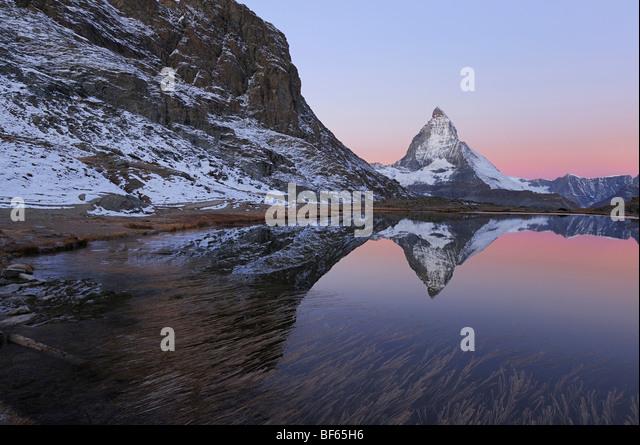 Matterhorn at sunrise in winter with reflection in the Riffelsee, Zermatt, Valais, Switzerland, Europe - Stock Image