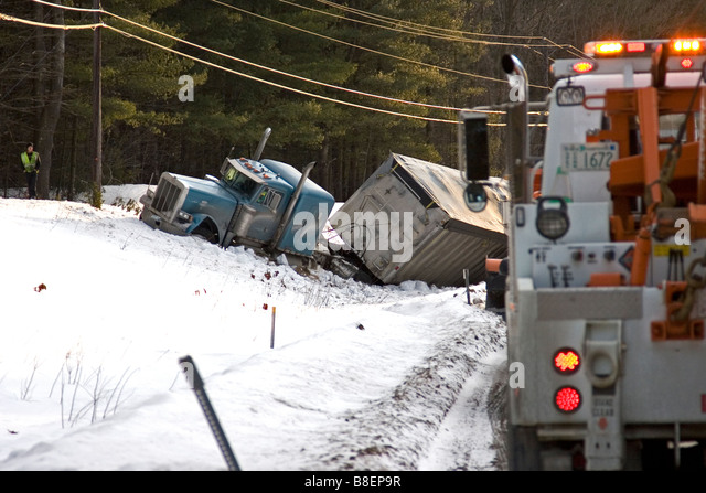A tow truck arrives at the scene of a lorry accident. - Stock Image