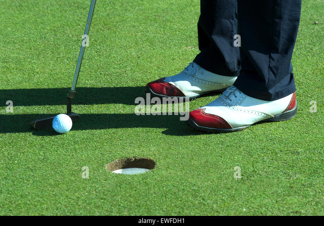Close up of person putting golf ball on golf course - Stock Image