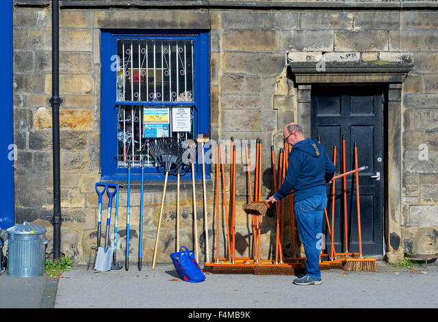Man choosing a broom outside a shop in Otley, West Yorkshire, England UK - Stock Image