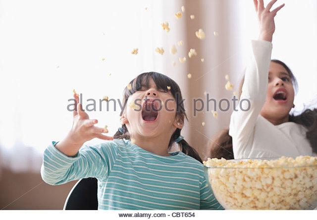 Playful girls throwing popcorn - Stock Image