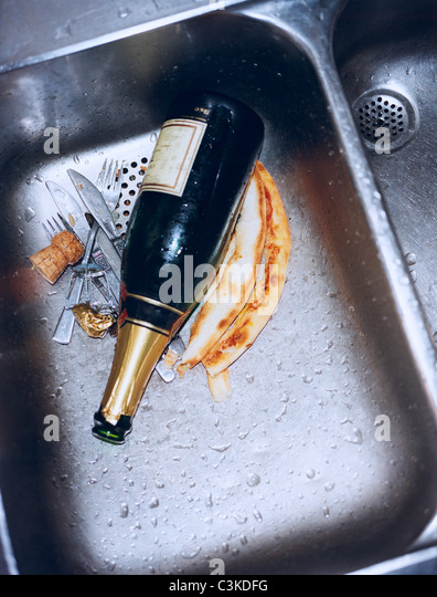 Champagne bottle and cutlery in sink, close-up - Stock-Bilder