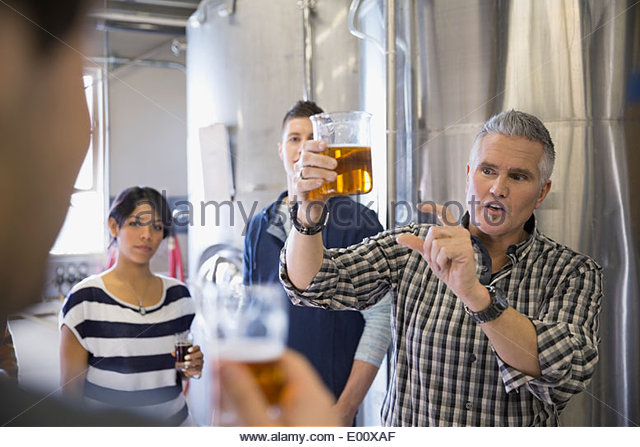 Brewery tour guide explaining beer in brewery - Stock Image