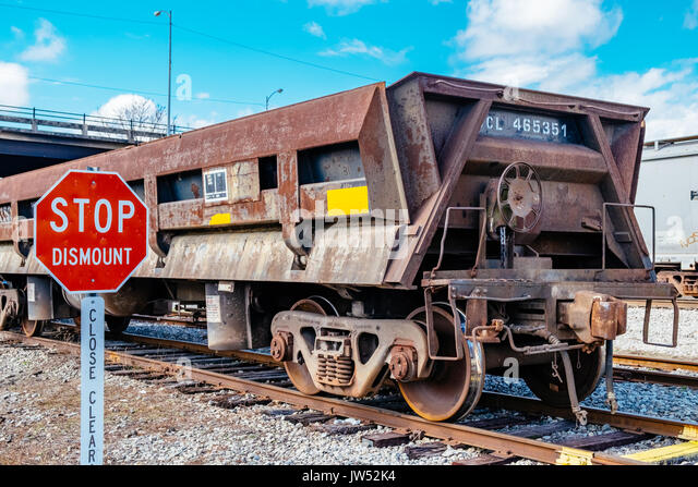 A rusted empty gondola railroad car, sitting on a siding spur in Opelika, Alabama, USA. - Stock Image