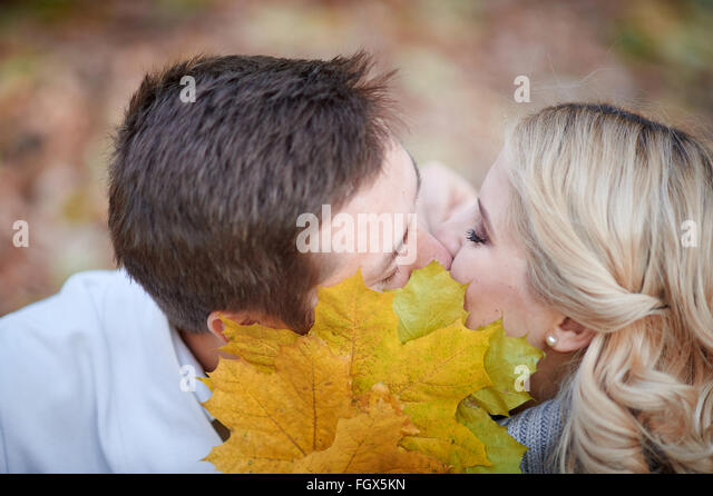 loving couple kissing in autumn park - Stock Image