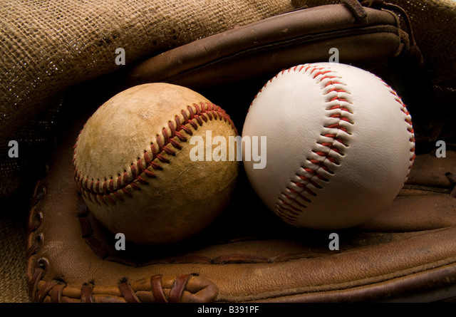 Old and new baseballs in glove - Stock Image